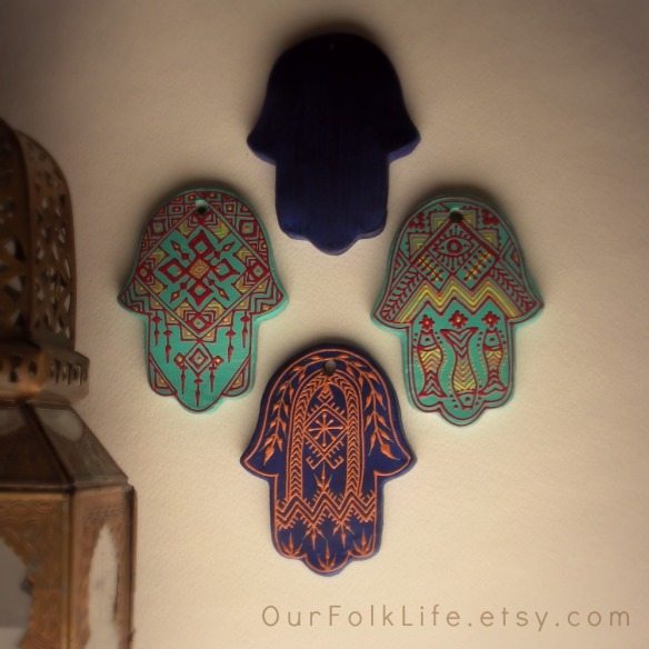 collection of hand painted clay hamsa to ward off the evil eye and attract good luck